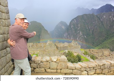Mature couple, pointing out a rainbow in Machu Picchu.