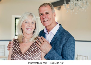 Mature couple posing for the camera while at a wedding.
