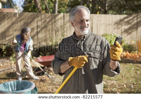 Mature couple raking autumn leaves and using a smart phone