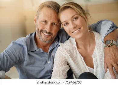 Mature couple relaxing at home, looking at camera