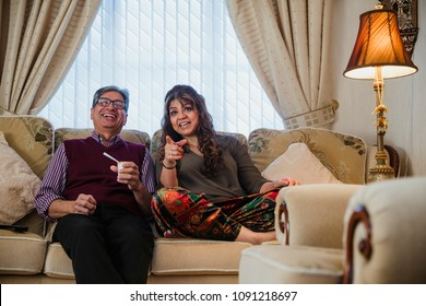 Mature couple are relaxing at home, watching television in the living room.