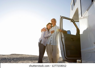Mature couple relaxing on motor home vacation at beach at camera