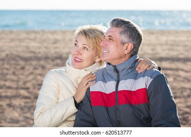 Mature couple relaxing together at a sea beach on sunny day. Focus on both persons
