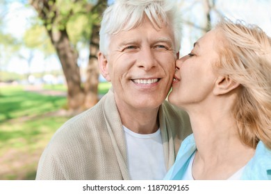 Mature couple resting in park on spring day