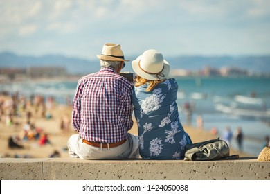 Mature couple of retired lovers enjoying retirement on the beach facing the sea with mobile cell phone taking pictures at sunset. Couple happy true love in the nature