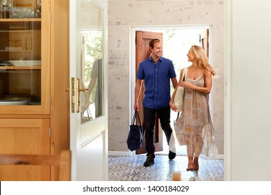 Mature Couple Returning Home From Shopping Trip Carrying Grocery Bags