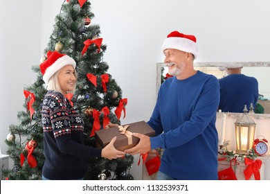 Mature couple in Santa hats with Christmas gift box at home