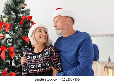 Mature couple in Santa hats at home. Christmas celebration