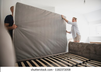 Mature couple are setting up their bed in their new home.