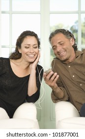 Mature couple sharing earphones while listening to music with an mp4 in their home's living room.