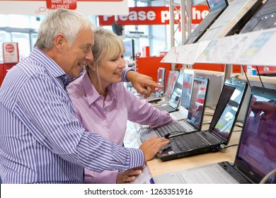 Mature couple shopping for laptop computer in electrical store