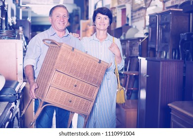 Mature couple is shopping the old nightstand in the antique store