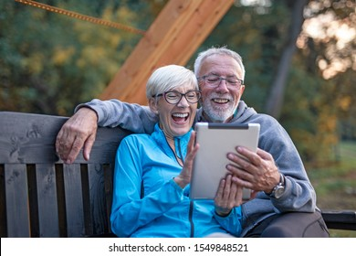 Mature couple sitting at banch in par and looking at tablet and having fun