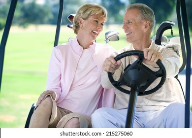 Mature couple sitting in golf buggy on golf course, man driving, smiling, front view