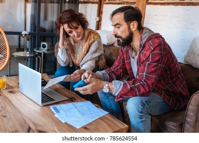 Mature couple sitting at home looking at their finance problems