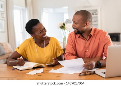 Mature couple sitting and managing expenses at home. Happy african man and woman paying bills and managing budget. Black smiling couple checking accountancy and bills while looking at each other.