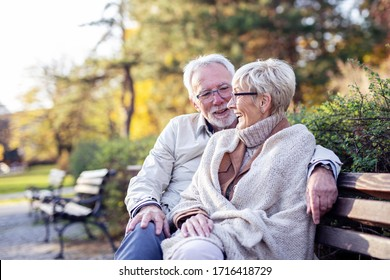 Mature couple sitting on bench in public park talk and smile