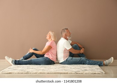 Mature couple sitting on floor near color wall in empty room. Moving into new house