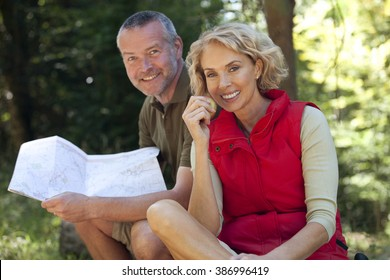 A mature couple sitting outdoors resting, man holding a map