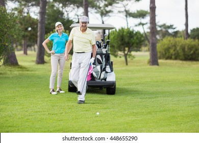 Mature couple standing at golf course