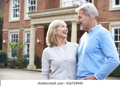 Mature Couple Standing Outside Home