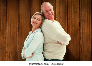 Mature couple standing and smiling at camera against wooden planks