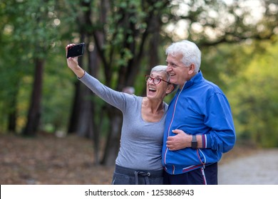 Mature couple taking selfie by mobile phone after jogging at the park