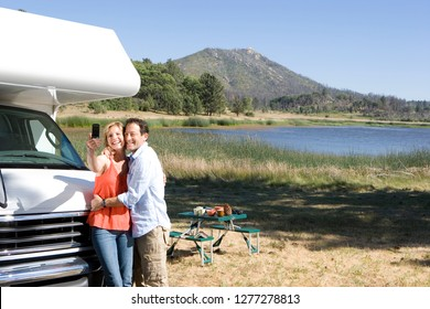 Mature couple taking selfie in countryside on motor home vacation