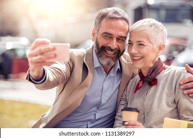 Mature couple taking selfie outdoors with smart phone.