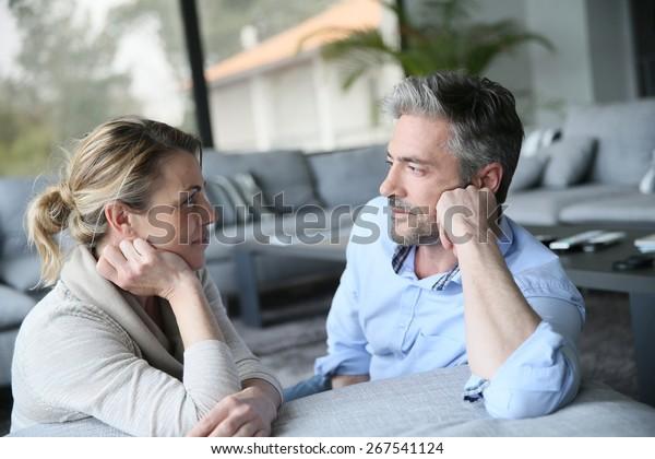 ソファで話し合う成熟した夫婦