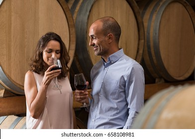 Mature couple tasting a glass of red wine in a traditional cellar surrounded by wooden barrels. Happy mature woman smelling a glass of red wine. Loving couple tasting wines in winery cellar.