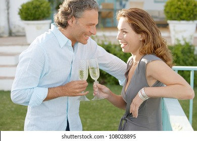 Mature couple toasting with champagne while in a hotel's garden.