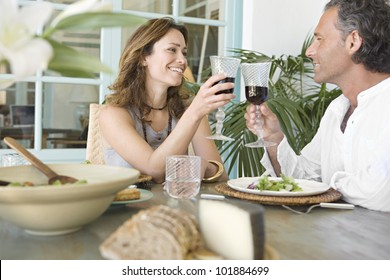 Mature couple toasting with red wine while having lunch at their vacation home.