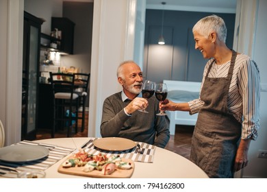 Mature couple toasting with wine in the dining room