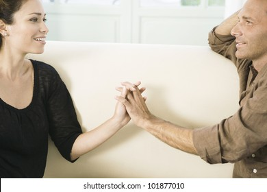 Mature couple touching hands while sitting on a white sofa at home.
