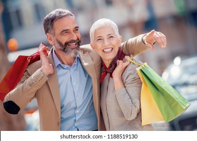 Mature couple of tourists enjoying in shopping together.