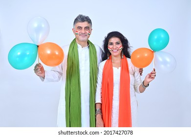 Mature couple in Tradional wear with orange and green  dupatta holding tricolor balloons in patriotic mood on the occasion of Independence day India celebrations studio shot - Shutterstock ID 2017427078