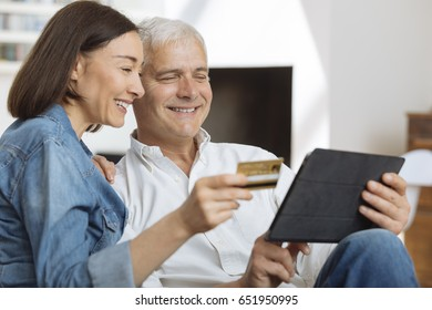 Mature couple using credit card to shop online