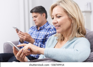 Mature Couple Using Digital Devices At Home