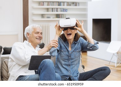 Mature couple using digital tablet and virtual reality headset in living room