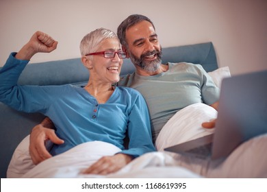 Mature couple using laptop together in bed at home.