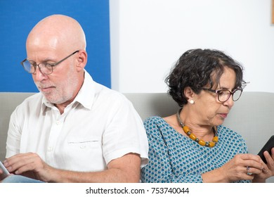 a mature couple using smartphone and tablet