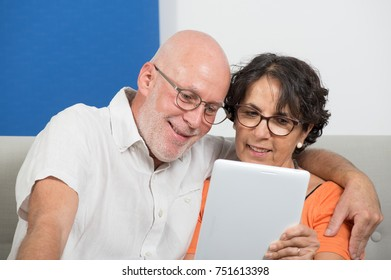 a mature couple using a tablet and smiling