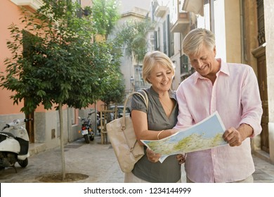 Mature couple visiting picturesque city street on holiday, reading map sightseeing, joyful smiling, sunny outdoors. Senior people travel leisure recreation lifestyle, retirement activities.