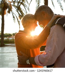 Mature couple visiting tropical palm trees avenue on holiday, hugging romance against the sun smiling, sunset outdoors. Senior people travel leisure recreation lifestyle, retirement activities.