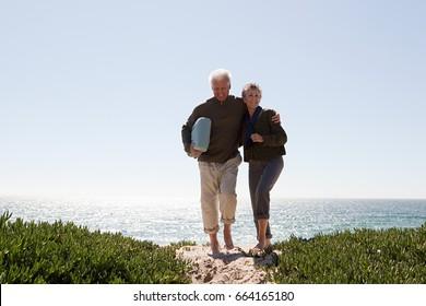 Mature couple walking over dune