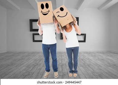 Mature couple wearing boxes over their heads against big room with several frames at wall