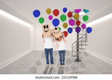 Mature couple wearing boxes over their heads against digitally generated room with winding staircase