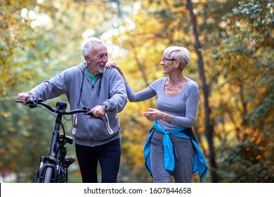 Mature couple woman and man with bicycle walking in the park and talk