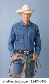 Mature cowboy against blue background in denim jeans and denim shirt holding a rope looking to camera